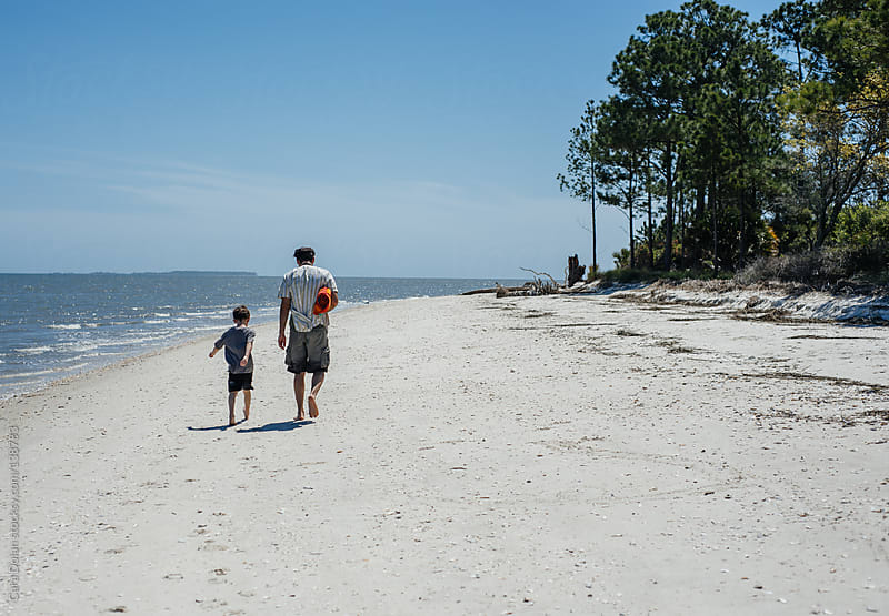 Father and son walk together on a beach by Cara Dolan for Stocksy United
