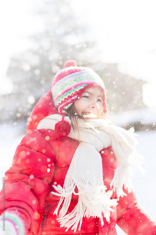 Young girl wearing red coat tossing snow in the air by Amanda Worrall for Stocksy United