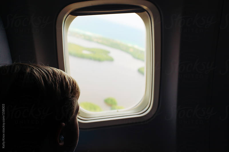 young child looking out of an airplane window by Kelly Knox for Stocksy United