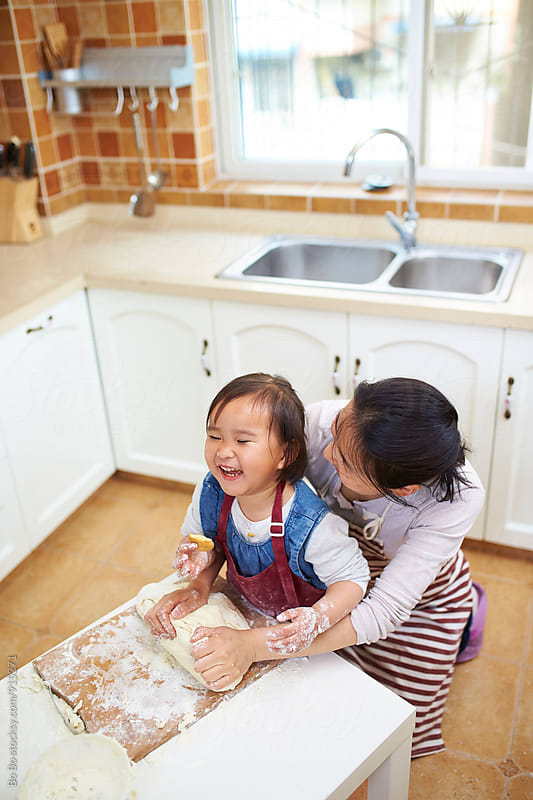 little asian girl having fun with her mother in the kitchen by cuiyan Liu for Stocksy United