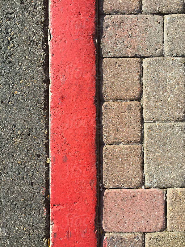 Red curb along urban sidewalk and street, close up by Paul Edmondson for Stocksy United
