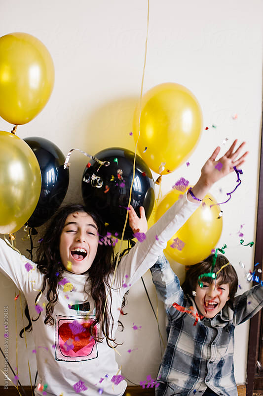 Siblings having fun together with confetti and balloons by Beatrix Boros for Stocksy United