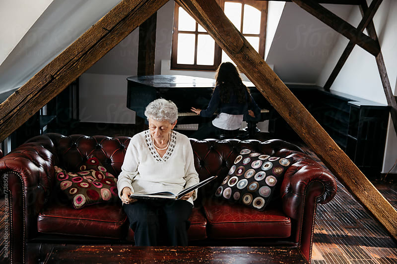 Mature woman reading on the sofa, while her granddaughter playing the piano by Beatrix Boros for Stocksy United
