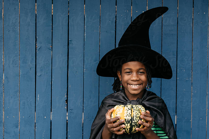 Smiling black girl in witch halloween costume holding a gourd by Gabriel (Gabi) Bucataru for Stocksy United