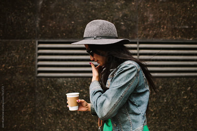 young woman wearing a hat and sunglasses, holding a cup of coffee and walking.  by Joe+Kathrina for Stocksy United