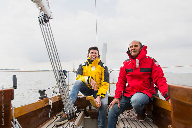 Young man steering a wooden sailboat, wearing a yellow sailing jacket. Sailing with his compagnon. by Ivo de Bruijn for Stocksy United