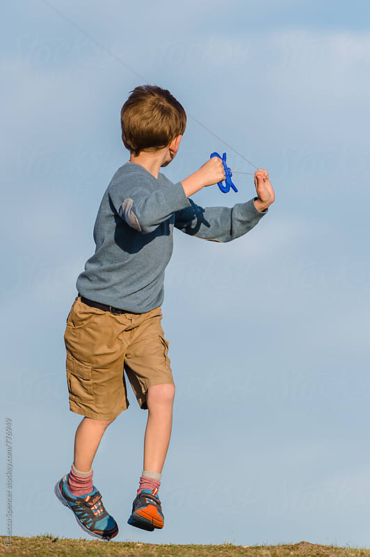 Boy leaps into the air by Rebecca Spencer for Stocksy United