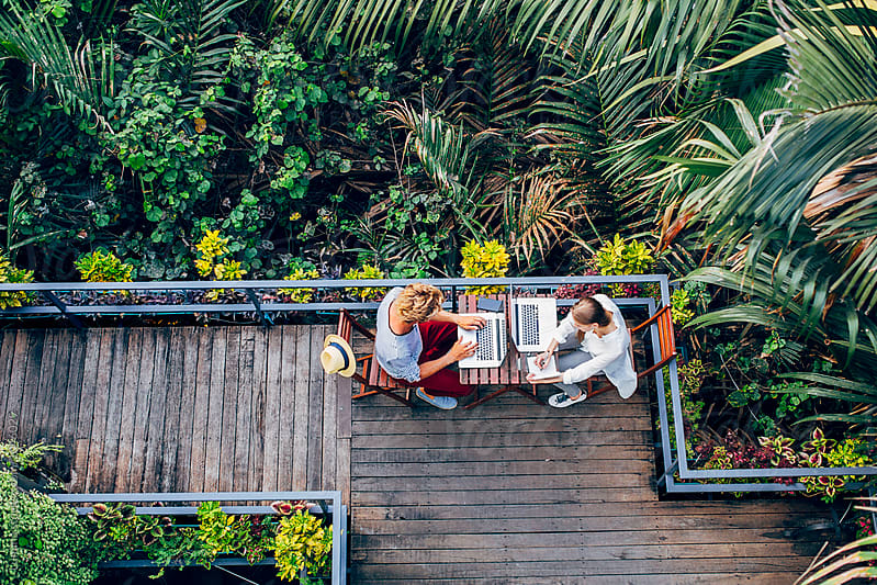 Man and Woman Working on Vacation in a Tropical Area by Lumina for Stocksy United