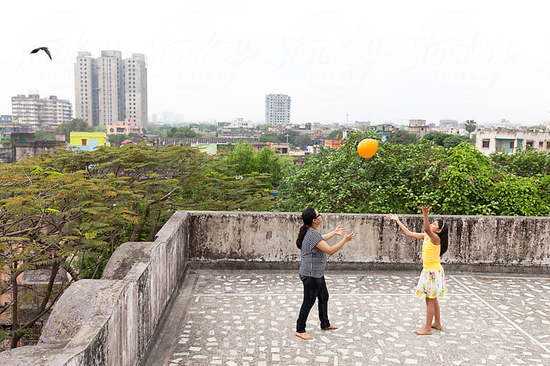 Teenage girls playing and making fun with balloon at rooftop by PARTHA PAL for Stocksy United
