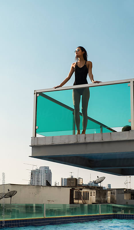 Attractive young female in black tricot standing on balcony above the swimming pool. by Marko Milanovic for Stocksy United