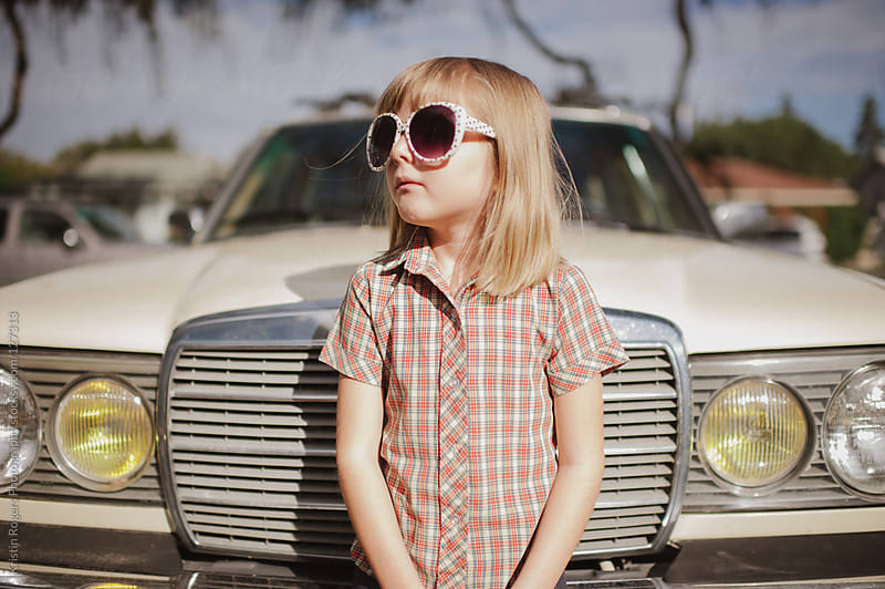 young girl standing in front of old car with sunglasses on by Kristin Rogers Photography for Stocksy United