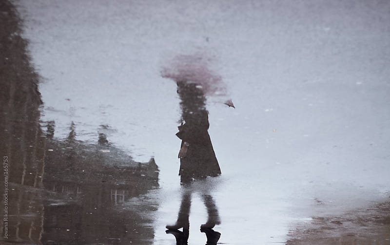 Silhouette puddle reflection of girl standing and holding umbrella by Jovana Rikalo for Stocksy United