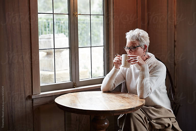 Mature woman relaxing with tea by window by Trinette Reed for Stocksy United