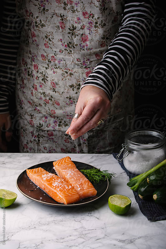 Woman preparing a salmon meal:Woman seasoning salmon fillets. by Darren Muir for Stocksy United