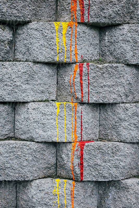 Red, orange and yellow paint dripping down brick wall by Paul Edmondson for Stocksy United