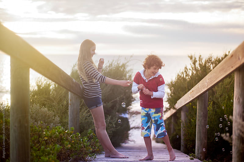 Boy and girl blowing bubbles on beach boardwalk at sunset by Angela Lumsden for Stocksy United