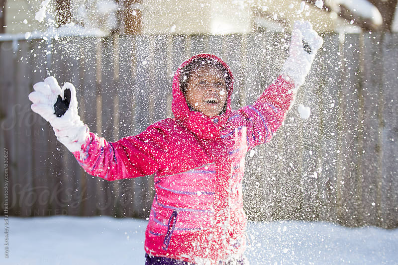 Tween girl playing and throwing snow into the air by anya brewley schultheiss for Stocksy United