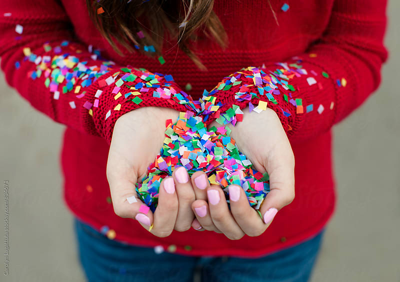 Girl holding a handful of colorful, paper confetti by Carolyn Lagattuta for Stocksy United