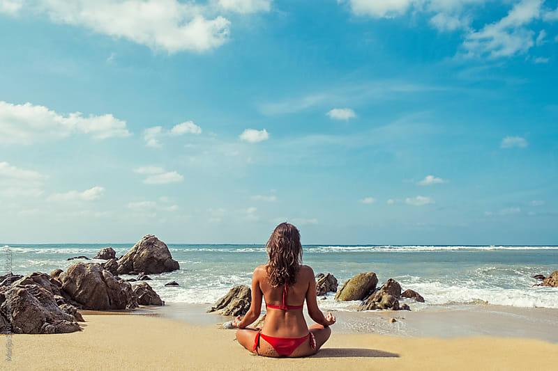 Woman meditating by the Ocean.  by Marija Savic for Stocksy United