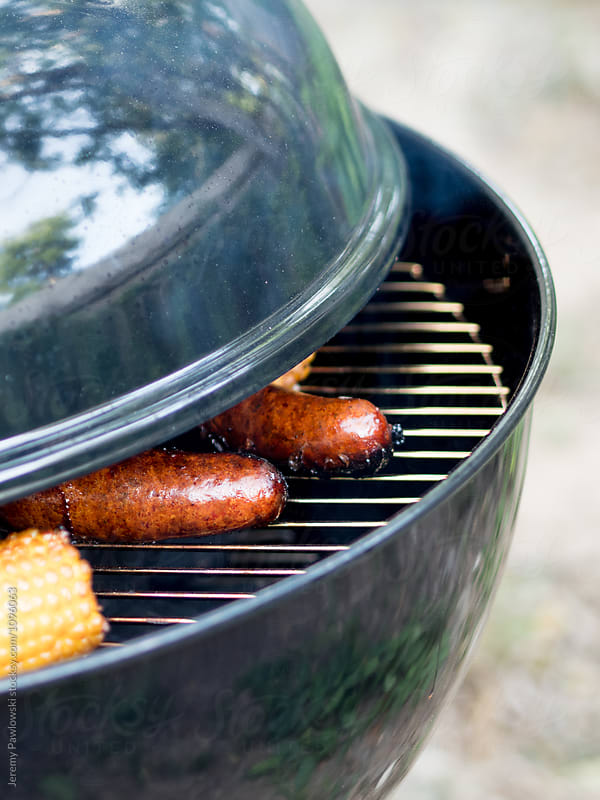 Uncovered grill with corn on the cob and sausage cooking by Jeremy Pawlowski for Stocksy United