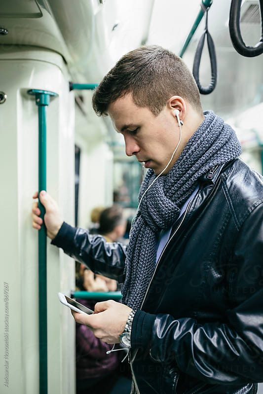 Young man using his smartphone with his headphones plugged in, in the subway by Aleksandar Novoselski for Stocksy United