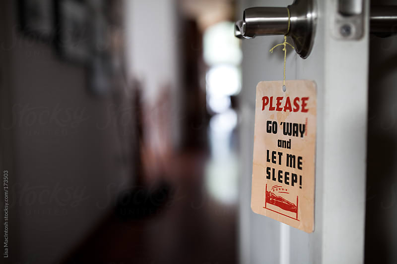 please go away and let me sleep vintage sign hanging on door knob by Lisa MacIntosh for Stocksy United