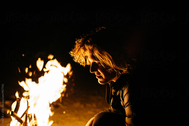 Man with curly long hair sitting by a fire on the beach at night by KATIE + JOE for Stocksy United