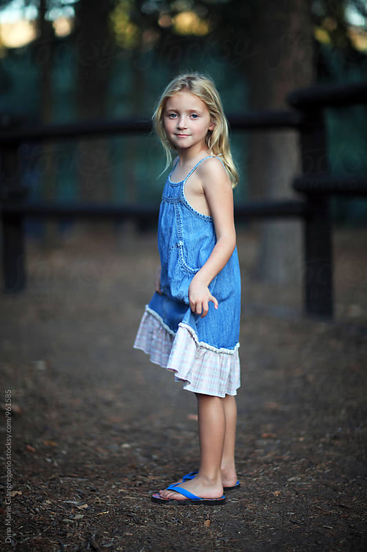 Blonde Girl Holding Edges Of Denim Dress Up by Dina Giangregorio for Stocksy United
