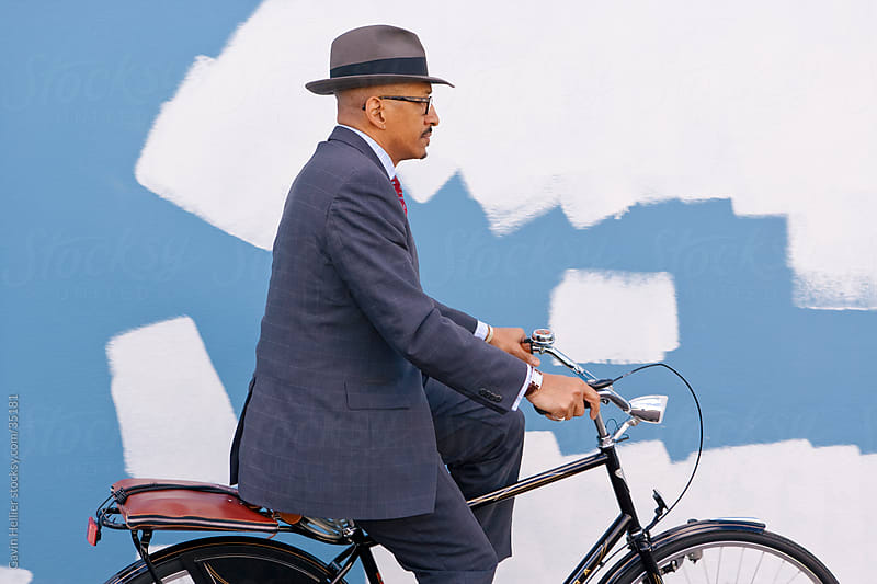 Bermuda, Atlantic Ocean, Hamilton, Businessman riding his bicycle in front of a colourfully painted wall  by Gavin Hellier for Stocksy United