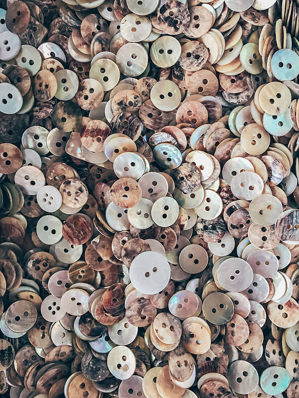 Background or texture of a pile of nacre buttons  by Vera Lair for Stocksy United