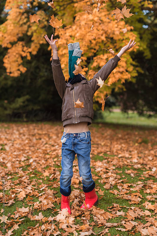 Happy boy throwing leaves in the air in front of trees of autumn colors by Rebecca Spencer for Stocksy United