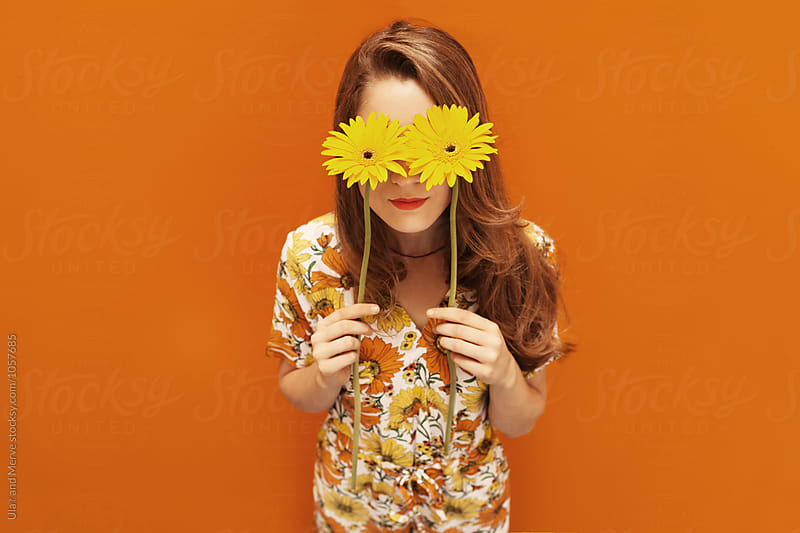 young woman dressing floral pattern jumpsuit in front of an orange wall by Ulaş and Merve for Stocksy United