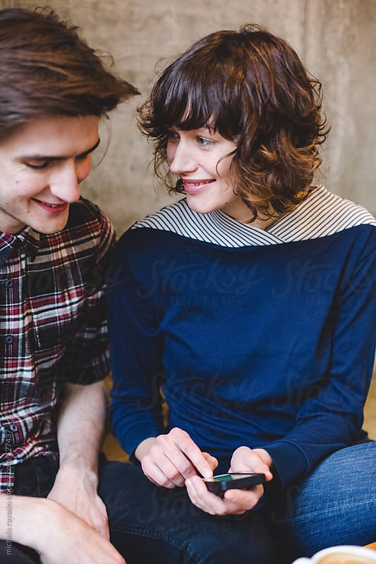 Young couple using a mobile phone by michela ravasio for Stocksy United