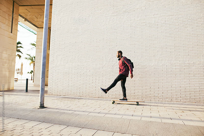 Side view of a man riding on longboard on the street. by BONNINSTUDIO for Stocksy United