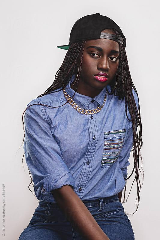 A pretty black girl with braids and a backward baseball cap by Ania Boniecka for Stocksy United