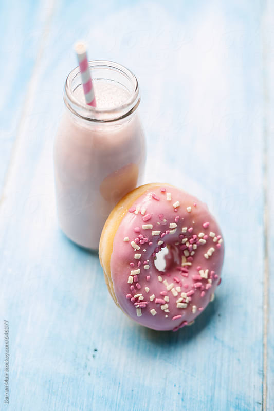 Pink glazed doughnut and a milkshake on a blue background. by Darren Muir for Stocksy United