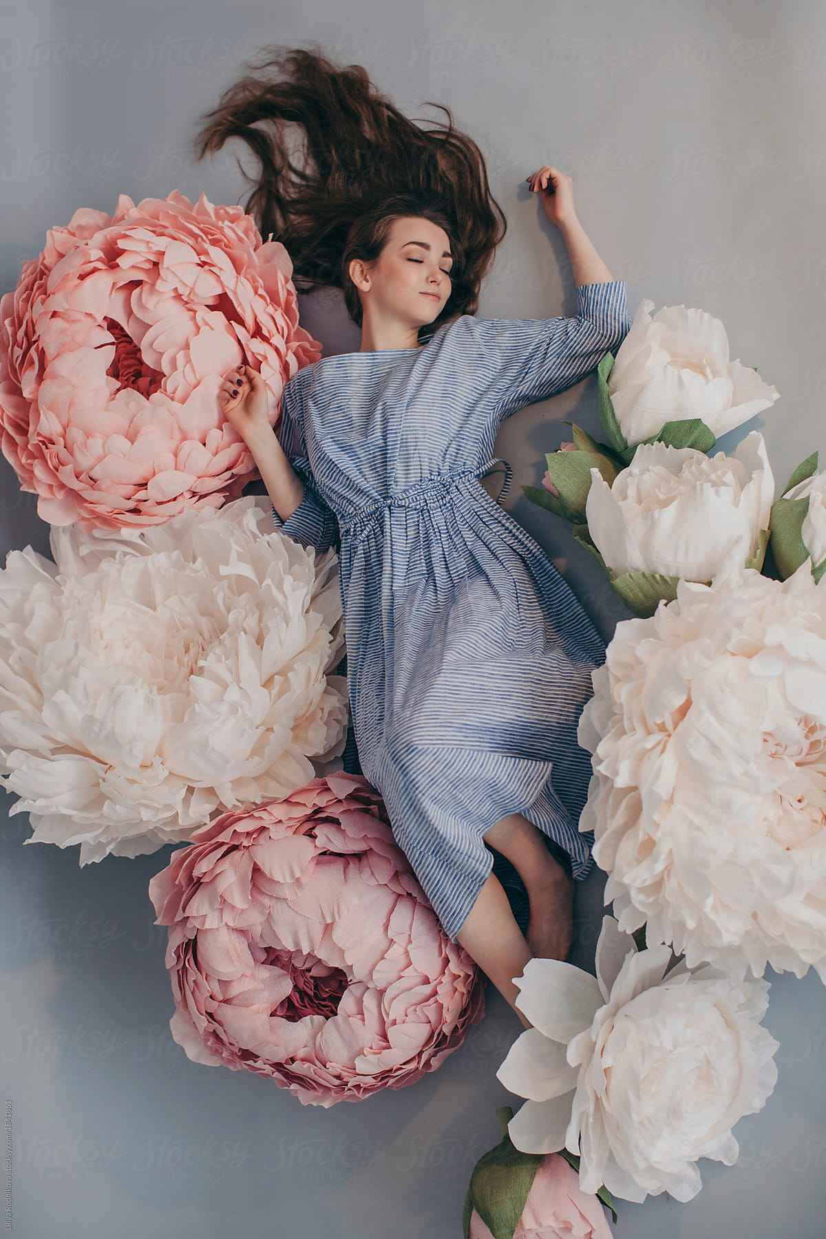 From above dreamy portrait of sleeping girl with long beautiful hair from above dreamy portrait of sleeping girl with long beautiful hair among the big paper peonies izmirmasajfo
