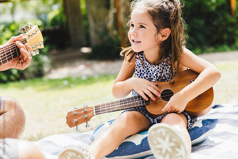 Young pretty girl playing with guitar at picnic in the park by Image Supply Co for Stocksy United