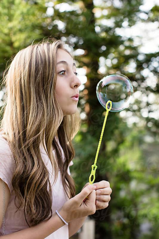 Beautiful teenage girl blowing bubbles by Carolyn Lagattuta for Stocksy United