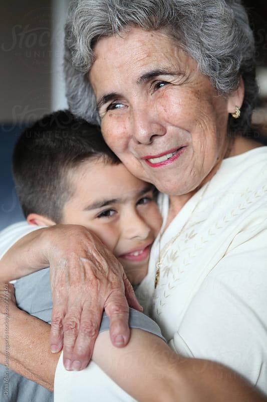 Hispanic Grandma Hugging Grandson by Dina Giangregorio for Stocksy United
