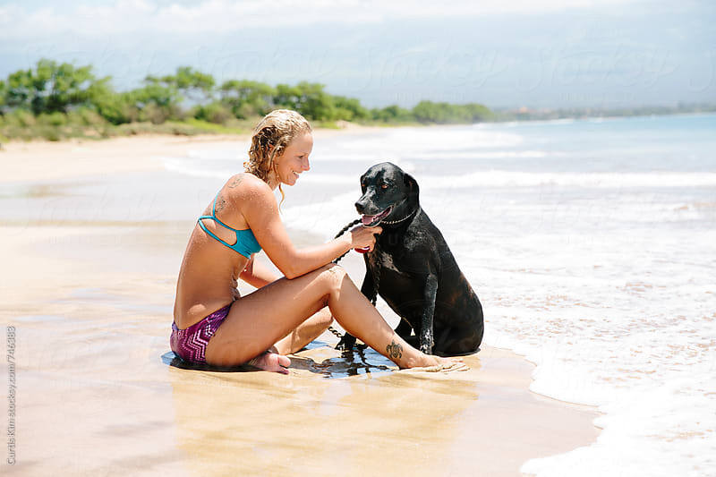 Beautiful blonde woman with her dog at the beach by Curtis Kim for Stocksy United