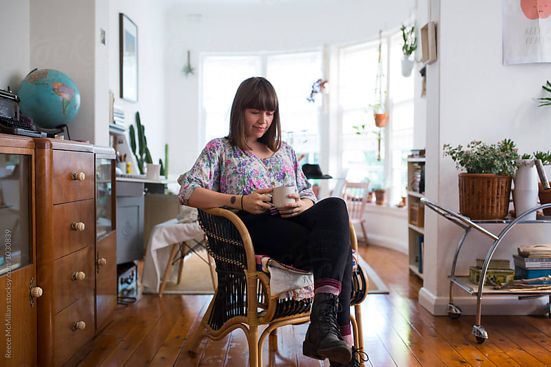 A young woman sitting in her apartment with tea by Reece McMillan for Stocksy United