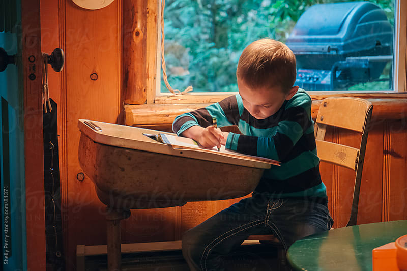 Preschool boy coloring at home  on an old school desk by Shelly Perry for Stocksy United