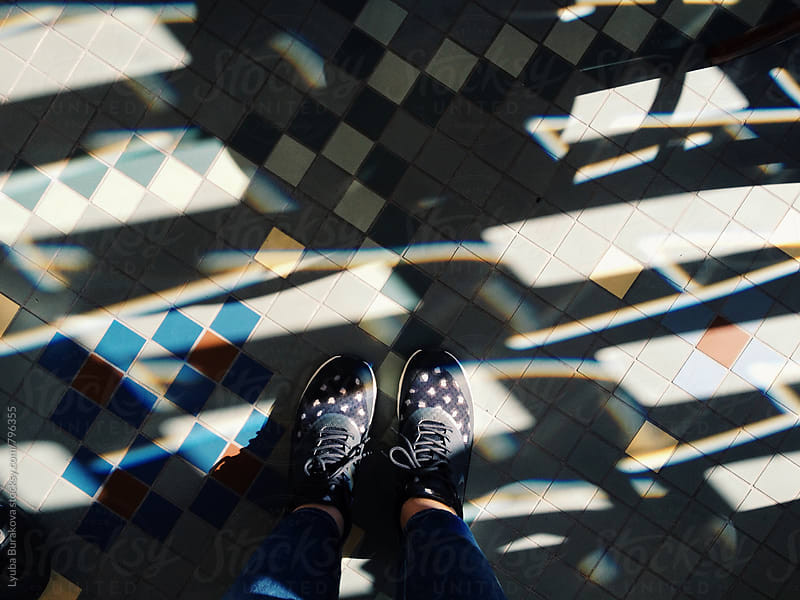 Woman wearing sneakers standing on tiles floor in contrast light  by Lyuba Burakova for Stocksy United