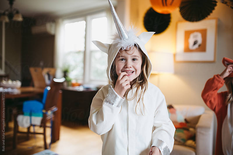 Girl in unicorn costume staring at camera by Rob and Julia Campbell for Stocksy United