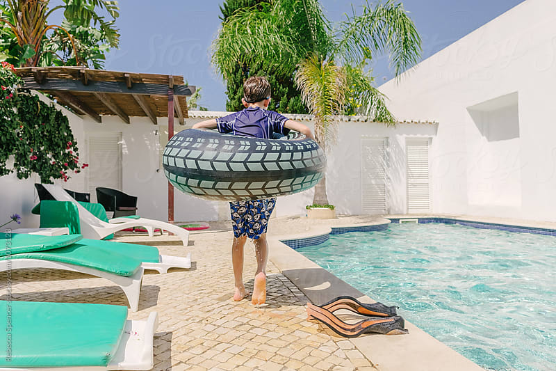 Boy wearing inflatable ring walks by swimming pool by Rebecca Spencer for Stocksy United