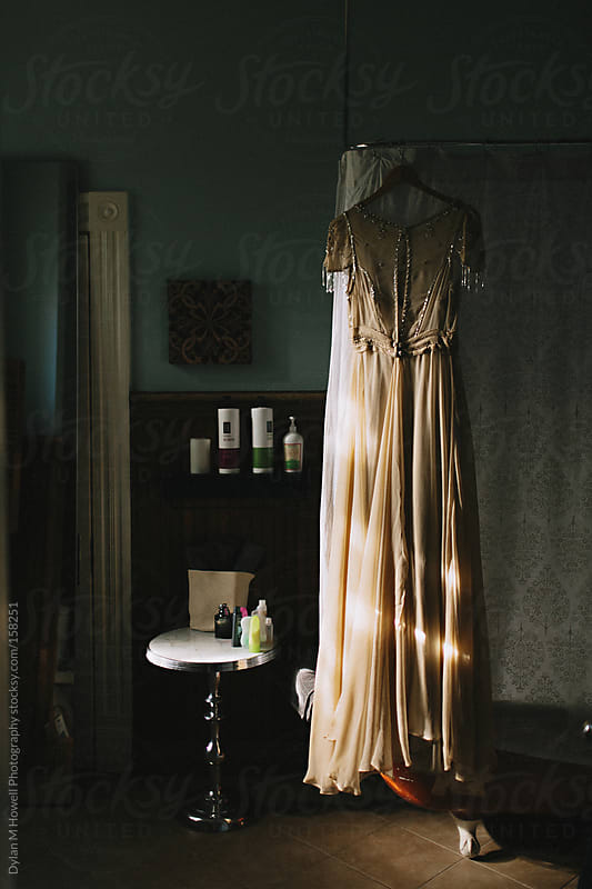 wedding dress hanging in room by Dylan M Howell Photography for Stocksy United