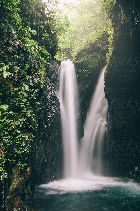 Waterfall on jungle setting. Slow shutter speed water effect by Alejandro Moreno de Carlos for Stocksy United