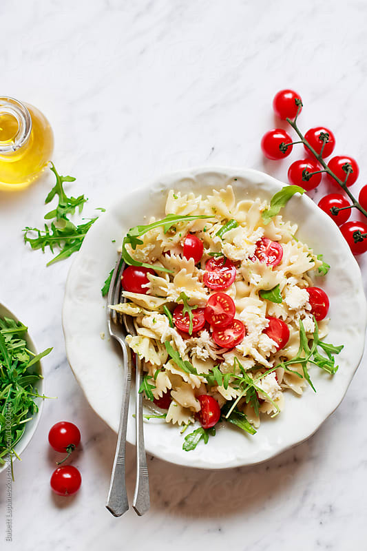 Pasta salad with arugula pesto and cherry tomatoes by Babett Lupaneszku for Stocksy United
