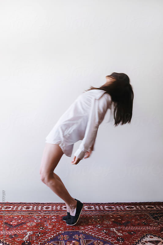 Unrecognisable woman leaning backwards, with intentional movement and blur by Jacqui Miller for Stocksy United